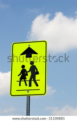 A street sign indicating that people are crossing ahead, isolated on a blue sky with some sporadic clouds.