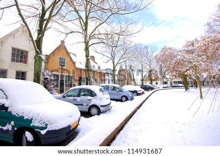 a street with houses and cars are covered with snow in wintertime - stock photo