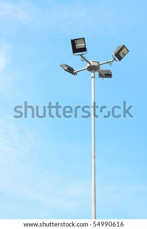 A streetlamp 4 way light with little cloud sky.