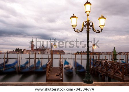 A streetlight on the edge of Piazza San Marco in Venice.  The view overlooks the island of San Giorgio Maggiore.  A long exposure making the gondolas in the foreground blur.