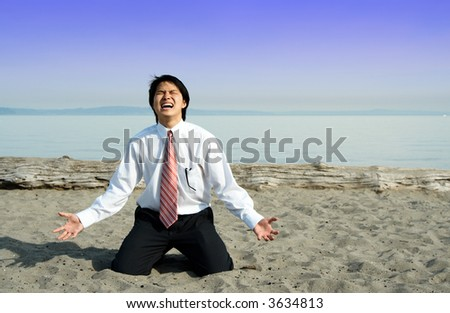 A stressed and frustrated businessman screaming on the beach