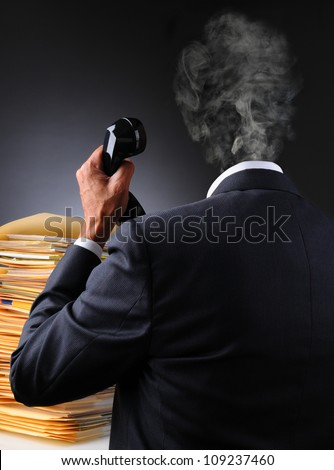 A stressed businessman with files and telephone as his head explodes into a puff of smoke. Vertical format over a dark to light background. Man is unrecognizable.