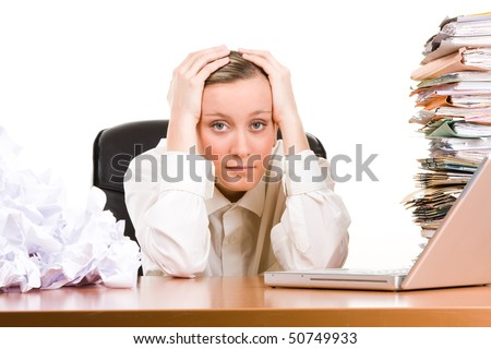 A stressed female executive with her head in her hands, sitting at her desk covered a pile of papers and stack of files. - stock photo