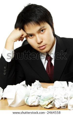 A stressed out businessman with crumpled paper all over table