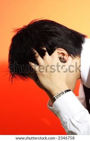 A stressed out businessman with hands covering his face