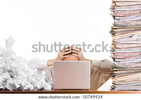 stock photo : A stressed person holding his head behind a laptop surrounded by a pile of files and papers,
