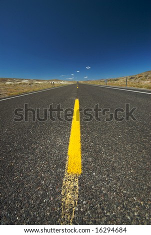 A stretch of wide open highway through the middle of the desert