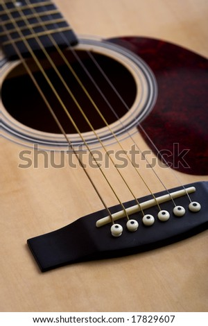 A 6-string acoustic guitar background with focus on the bridge, with copy space