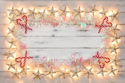 A string of golden star christmas lights, tinsel and candy sticks, on a destressed woodern background, creating a border around an empty space for copy