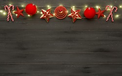 A string of red christmas decorations, lights and candy sticks, on a destressed dark woodern background