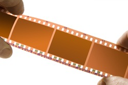 a strip of negative film held closeup in fingers