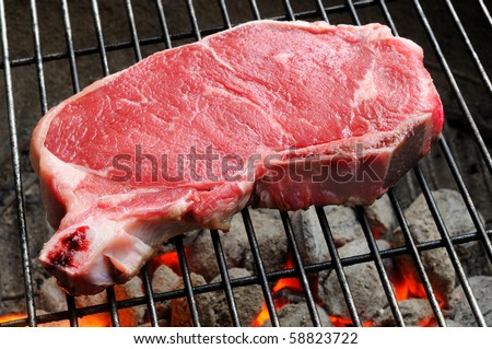 A strip steak newly placed on a charcoal grill