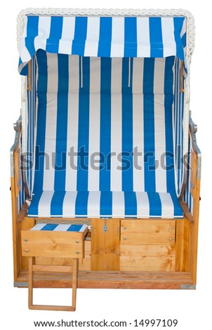a striped german beach chair. Strandkorb. on the beach on a sunny day. used on cold and hot days