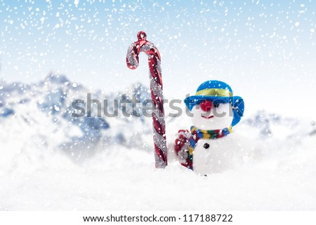 A stripy candy cane and snow man outdoor during Christmas season