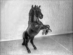 A strong and powerful stallion, perched on its hind legs in a black and white background.