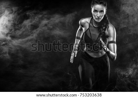 A Strong athletic, female runner on the black bacground wearing a tight, fitness outfit. #753203638