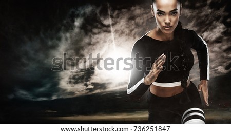A strong athletic, female sprinter, running at sunrise wearing in the sportswear, fitness and sport motivation concept with copy space.