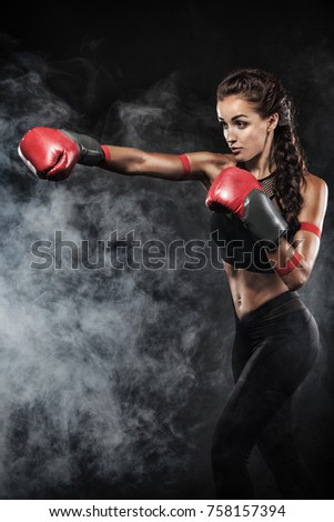 Stock Photo A strong athletic, woman boxer, boxing at training on the black background. Sport boxing concept with copy space.