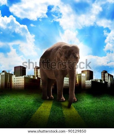 A strong, big elephant is in the middle of a city with clouds in the background. Use it for a strength or power concept.