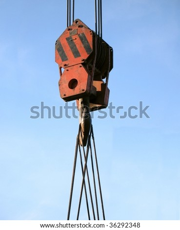 A strong hook of a crane that has a weight attached with steel cables