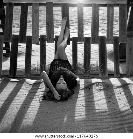 A strong image of a depressed and upset young woman laying outsideon the beach  with her hand in her head