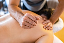 A strong male massage therapist giving a man a deep tissue massage. Physical therapy and chiropractic treatment concepts
