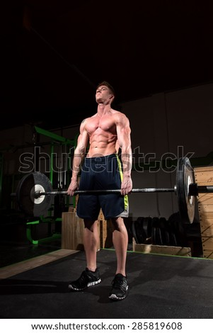 A strong man holding weights at a gym. I used dramatic lighting to get the sense of determination, focus, and motivation across.