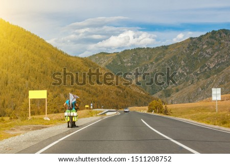 A strong man in helmet ride on sport bicycle with bags on a road in the mountains of the Altai climbing up by highway in autumn indian summer. Travelling and trip around the world. #1511208752