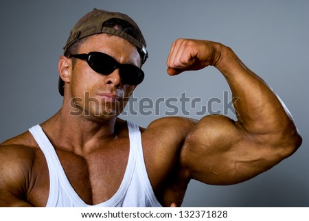 A strong man in sunglasses shows his muscles. Trained body. The gray background