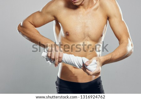 A strong man with a strong torso rolled up a towel on a gray background