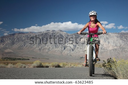 A strong woman rides along the road in the Sierra Nevavda of California.