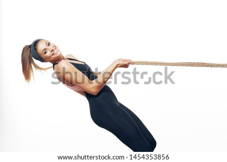 A strong woman with a strong torso and in dark clothes pulls the rope #1454353856