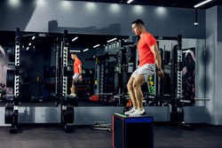 A strong young man with expressive muscle in his legs and arms has just landed on a stepper in the gym. Sportswear, personal training