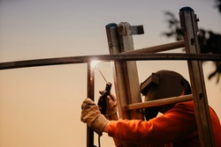 A structural steel worker working on a high rooftop for a modern house roof structure installation