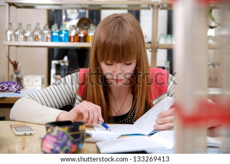 A student at work in laboratory of chemistry studies the records in a notebook