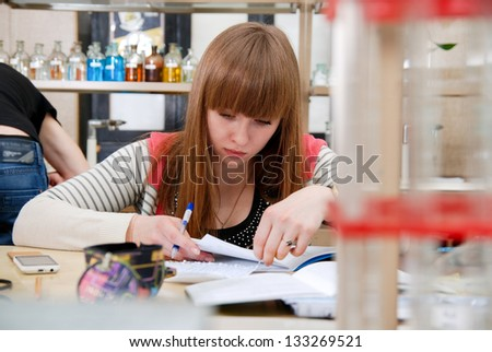 A student at work in laboratory of chemistry studies the records in a notebook.