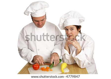 A student chef preparing food while a stern instructor looks on.   Isolated on white.