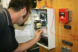 A student electrician wiring a fire alarm system at his technical college.