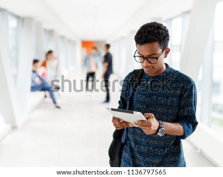 A student from India stands with a tablet at the University. Students in the background. The photo illustrates education, College, school, or University.