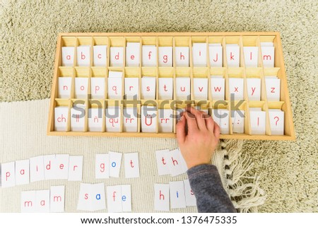 A student of a montessori school using cards with letters to compose words and phrases on a mat.