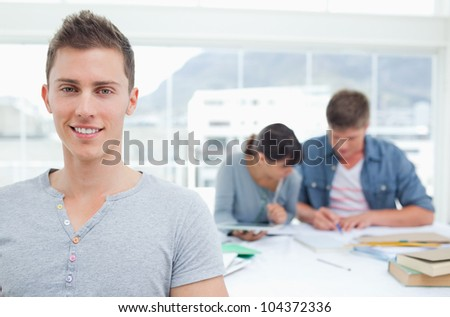 A student standing ahead of his friends as he smiles while they study together