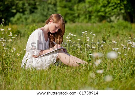 A student takes notes on a summer meadow
