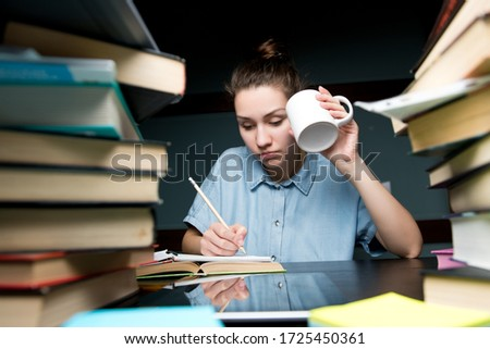 A student writes knowledge in a notebook and drinks coffee in the late evening. Girl prepares for university or colege exams Imagine de stoc ©