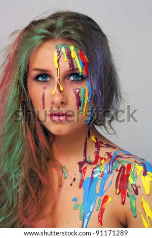 A studio close-up of a lovely young blonde with multicolored hair and several colors of paint poured and dripping on her.