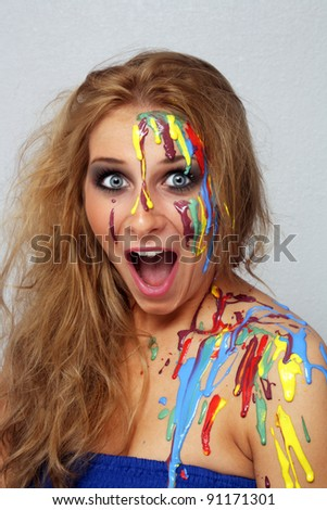 A studio close-up of an excited, lovely young blonde with several colors of paint poured and dripping on her.