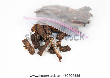A studio close up shot a clear plastic sandwich bag containing homemade spicy beef jerky on a white background.