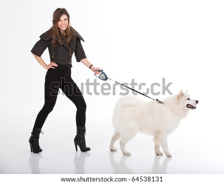 a studio image of a young woman, dressed in black, smiling, walking her white dog. they are both viewed from a side, with her looking to the camera and the dog in front of him. - stock photo