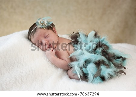 A studio portrait of a beautiful one week old baby girl sleeping,  wearing a blue and brown boa and flower headpiece
