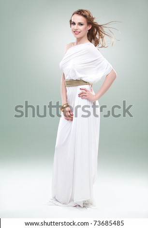 a studio portrait of a beautiful young woman, wearing a long, white, ancient greek inspired dress, smiling, with wind blowing in her hair.