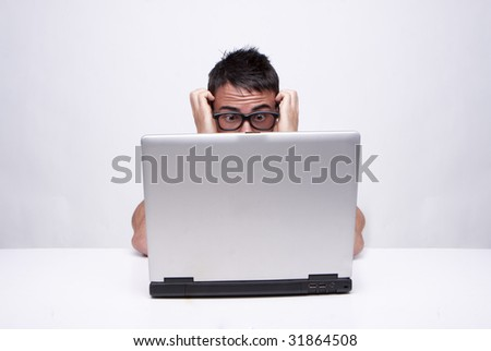 A studio portrait of a caucasian man looking desperate.Isolated on a white background wearing glasses working on his laptop